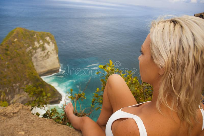 Young attractive and happy tourist woman looking the stunning view of beautiful sea cliff beach at viewpoint enjoying exotic. Lifestyle portrait of young stock photos