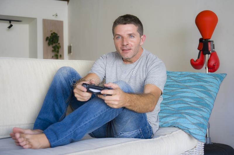 Lifestyle portrait of young attractive and happy guy enjoying playing video game at home living room sofa couch holding console co stock photo