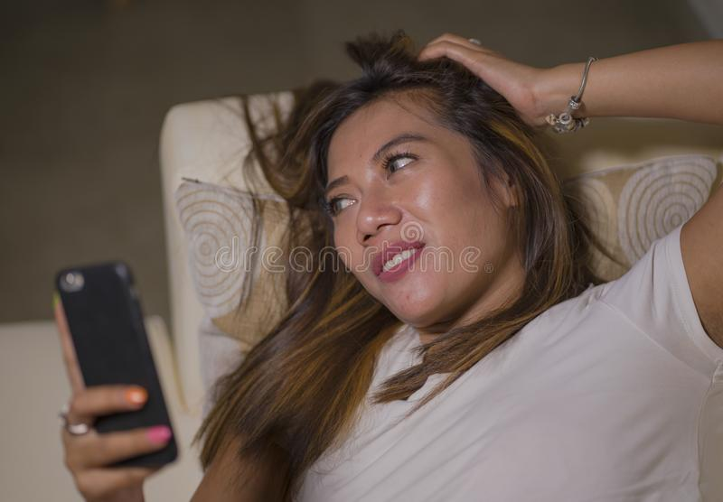 Lifestyle portrait of young attractive happy and relaxed woman enjoying homey at living room sofa couch using internet social. Media or dating app on mobile royalty free stock photo