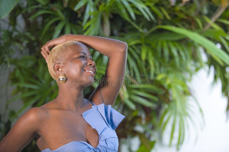 Lifestyle portrait of young attractive and joyful black afro american woman smiling happy posing cheerful at home terrace with gre. En plants background in royalty free stock photo