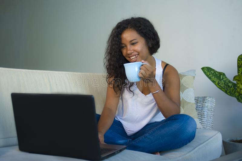 Young attractive and relaxed black african American student woman sitting at home sofa couch networking with laptop computer drink royalty free stock image