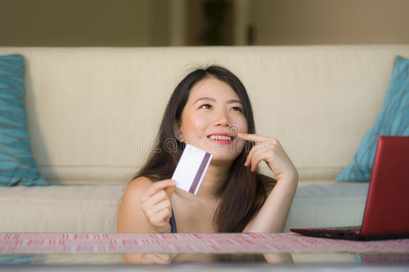 Lifestyle portrait of young beautiful and happy Asian Japanese woman holding credit card banking and online shopping with laptop c royalty free stock image