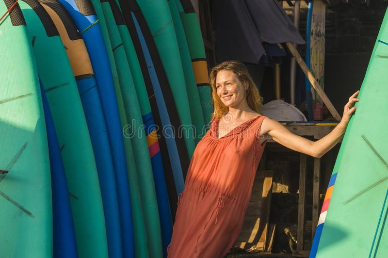 Lifestyle portrait of young beautiful and happy blond woman smiling relaxed and cheerful posing with colorful surf boards leaning royalty free stock photography