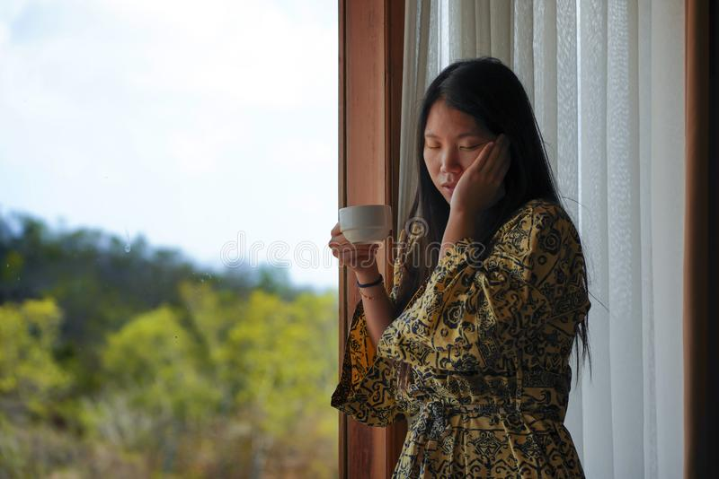 Lifestyle portrait of young beautiful happy and relaxed Asian Chinese woman in stylish bathrobe by luxury hotel room window having stock photography