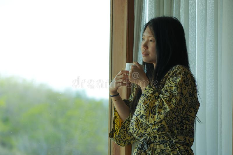 Lifestyle portrait of young beautiful happy and relaxed Asian Japanese woman in stylish bathrobe by luxury hotel room window stock images