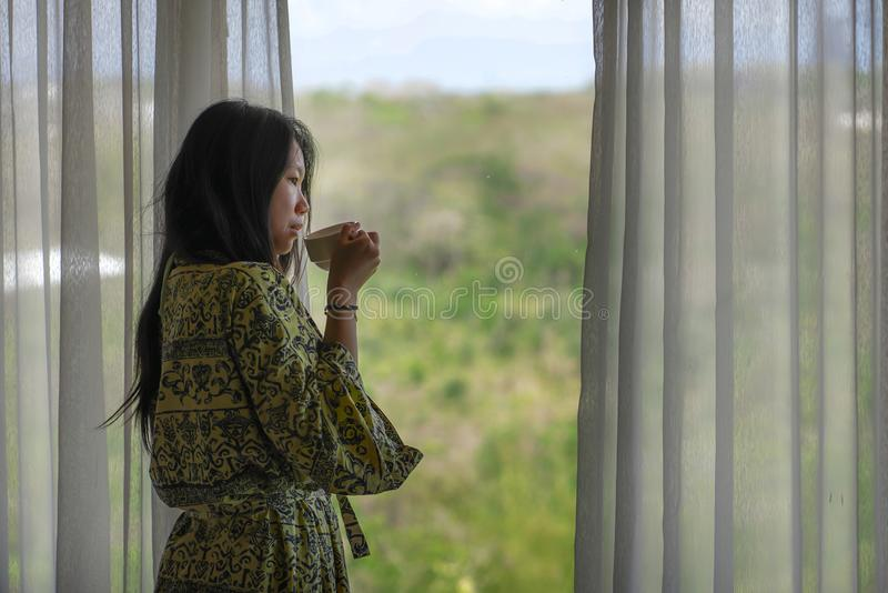 Lifestyle portrait of young beautiful happy and relaxed Asian Korean woman in stylish bathrobe by luxury hotel room window having royalty free stock photo