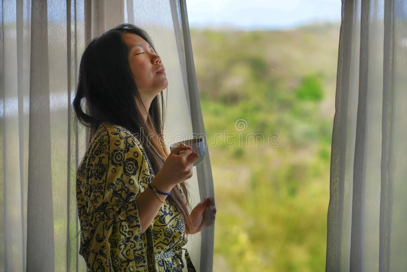 Lifestyle portrait of young beautiful happy and relaxed Asian Korean woman in stylish bathrobe by luxury hotel room window having stock image
