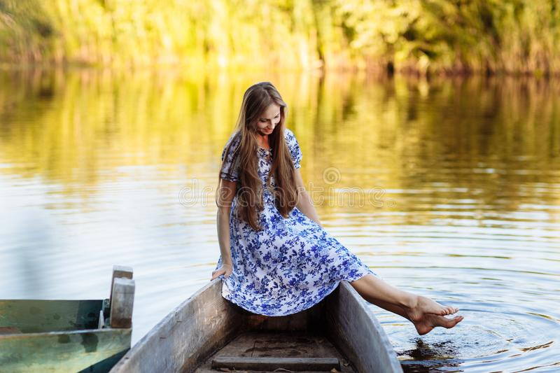 Lifestyle portrait of young beautiful woman sitting at motorboat. girl having fun at boat on the water royalty free stock image
