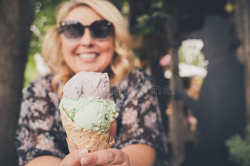 Lifestyle portrait of a young blond woman enjoying a waffle cone. Focus on ice cream cone, woman intentionally blurred royalty free stock images
