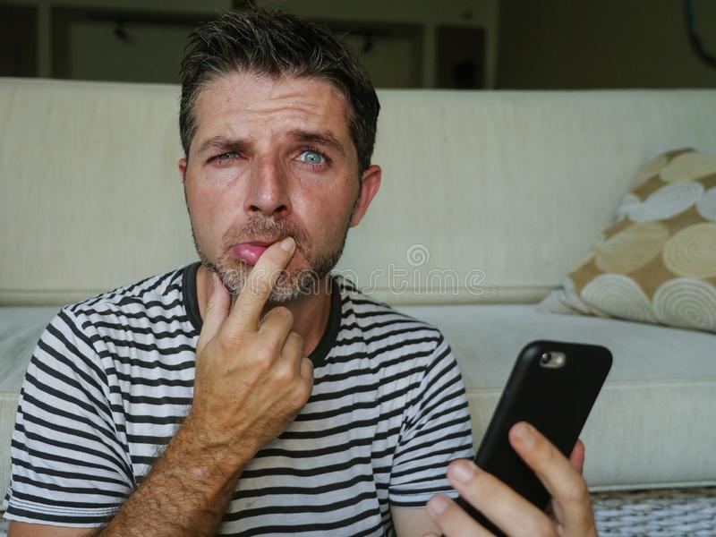 Lifestyle portrait of young confused and stressed hilarious man holding mobile phone looking funny and worried having some problem stock photos