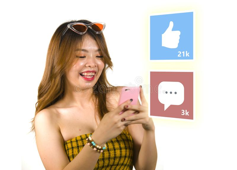 Lifestyle portrait of young happy and attractive Asian Chinese woman using internet mobile phone composite with social media app stock images