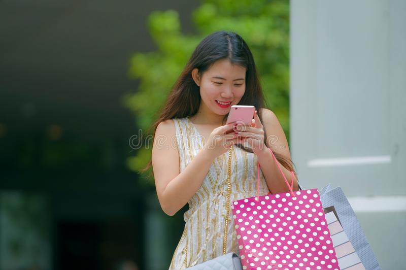 Young happy and beautiful Asian Chinese woman walking on the street carrying shopping bags using mobile phone searching online for royalty free stock photography