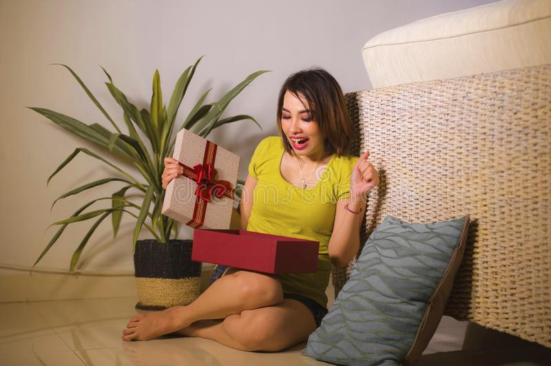 Lifestyle portrait of young happy and beautiful Asian Indonesian woman opening Christmas or birthday gift box with red ribbon royalty free stock photos