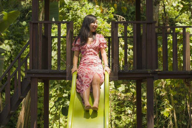 Lifestyle portrait of young happy and beautiful Asian Korean woman in sweet Summer dress playing on slide at city park smiling royalty free stock photography