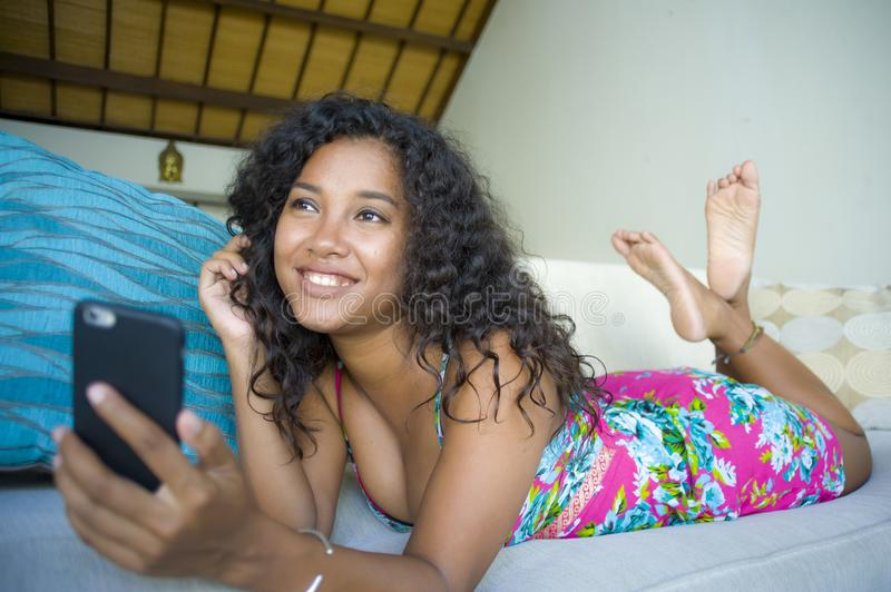 Lifestyle portrait of young happy and beautiful black african american woman at home using mobile phone networking and te. Xting relaxed on couch smiling stock photo