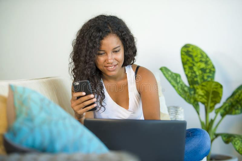 Lifestyle portrait of young happy and beautiful black african American woman using internet mobile phone while working on laptop royalty free stock photos
