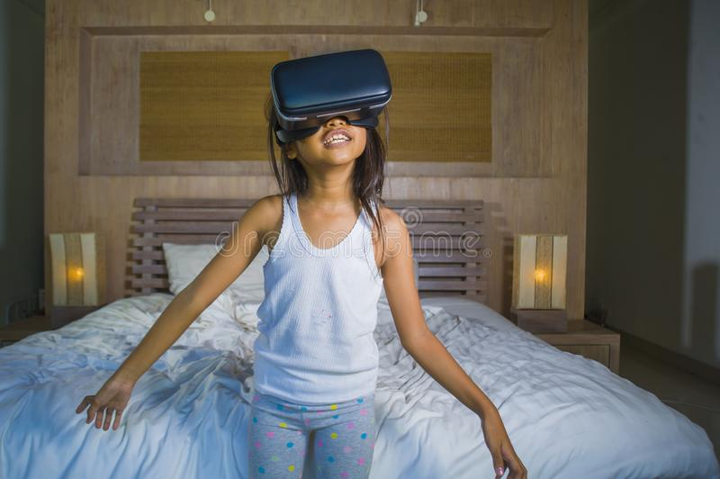 Lifestyle portrait of young happy and excited female child wearing VR goggles device headset playing virtual reality simulation. Game enjoying an amazing stock photos
