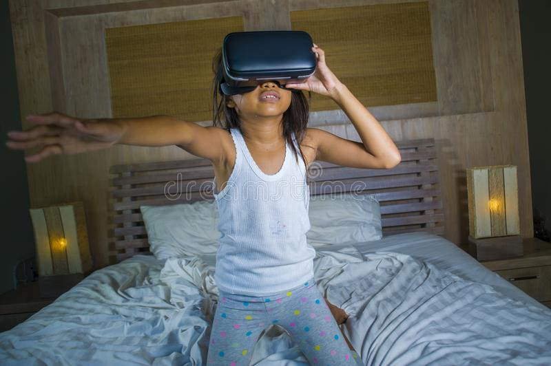 Lifestyle portrait of young happy and excited female child wearing VR goggles device headset playing virtual reality simulation. Game enjoying an amazing stock image