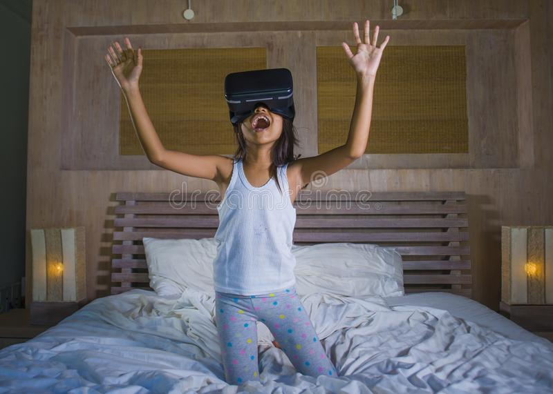 Lifestyle portrait of young happy and excited female child wearing VR goggles device headset playing virtual reality simulation. Game enjoying an amazing stock photography
