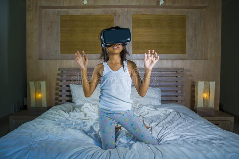 Lifestyle portrait of young happy and excited female child wearing VR goggles device headset playing virtual reality simulation. Game enjoying an amazing royalty free stock image