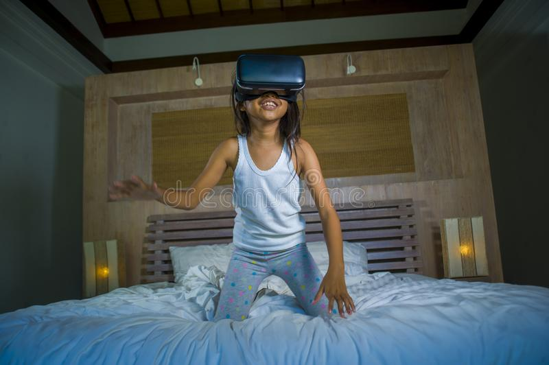 Lifestyle portrait of young happy and excited female child wearing VR goggles device headset playing virtual reality simulation. Game enjoying an amazing royalty free stock photo