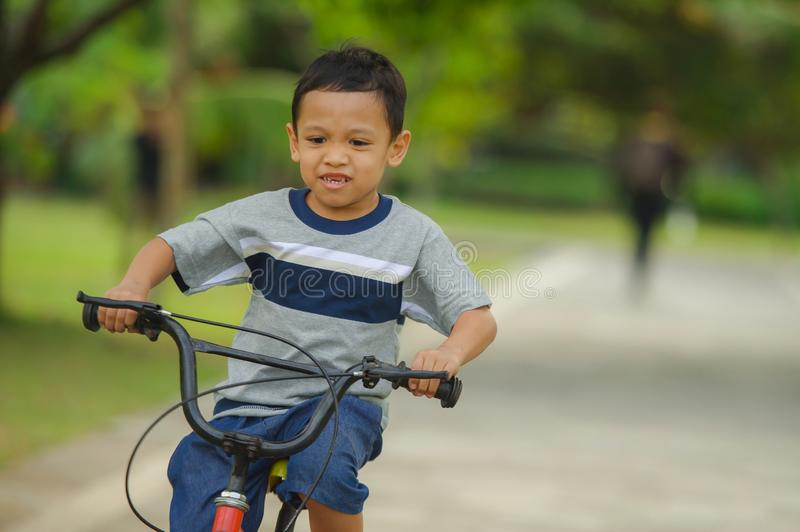 Lifestyle portrait of young happy and excited 5 years old Asian Indonesian child enjoying learning bike at city park isolated on. Trees background in kid having royalty free stock images