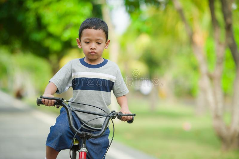 Lifestyle portrait of young happy and excited 5 years old Asian Indonesian child enjoying learning bike at city park isolated on. Trees background in kid having royalty free stock photography