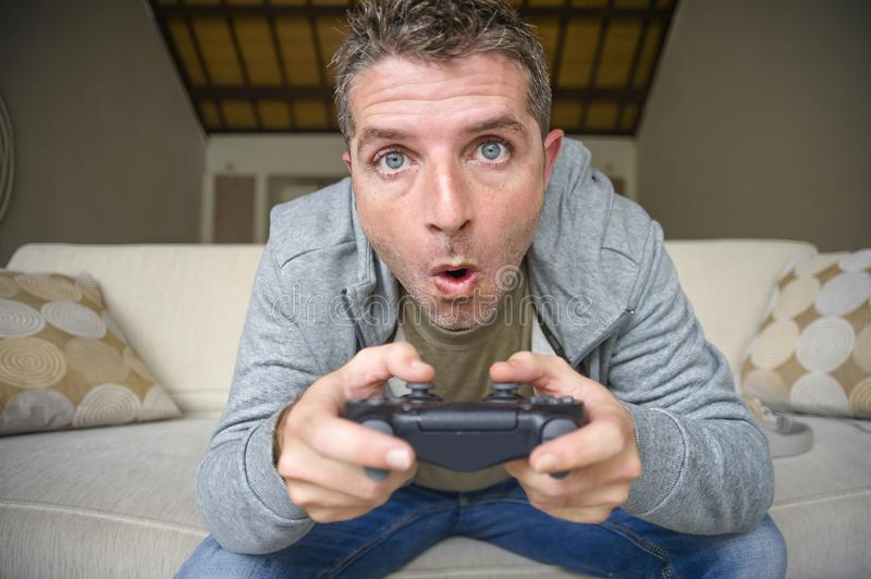 Lifestyle portrait of young stressed and excited gamer man playing video game at home living room having fun on sofa couch holding. Controller concentrated and royalty free stock photo