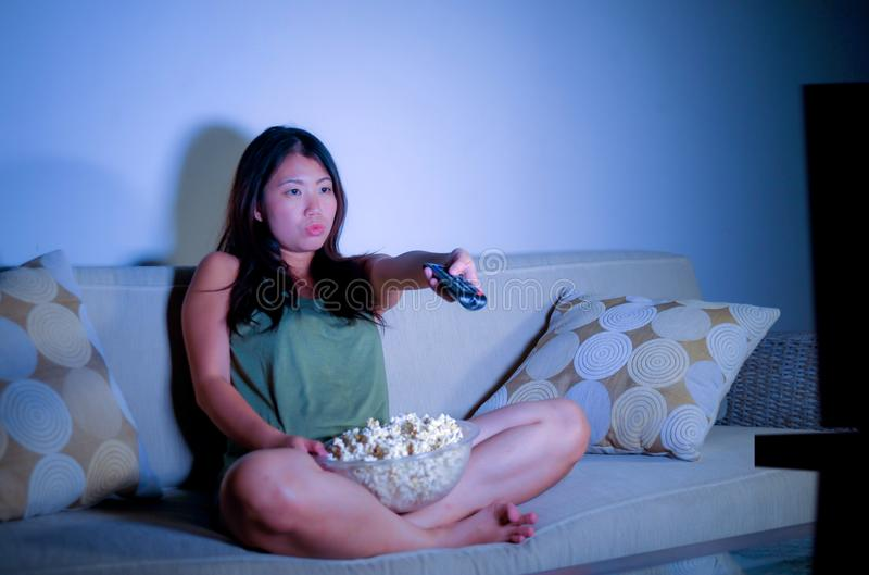 Lifestyle portrait of young sweet and happy Asian Korean woman enjoying watching television using remote control eating popcorn la royalty free stock images