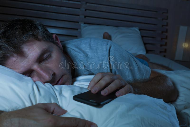 Lifestyle portrait of young tired and exhausted man sleeping or falling asleep while networking in bed late at night in internet stock photography