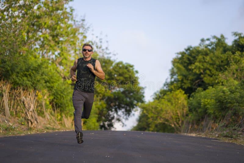 Lifestyle-portret van jonge, aantrekkelijke en gezonde man op zijn 30er of 40er jaren op landelijke weg met jogging-out training stock foto's