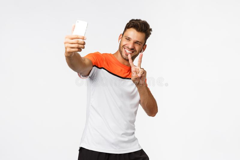 LIfestyle, sport and people concept. Cheerful handsome mascular male athlete in gym, wear sportswear, wireless. Headphones, taking selfie on smartphone, smiling royalty free stock photography