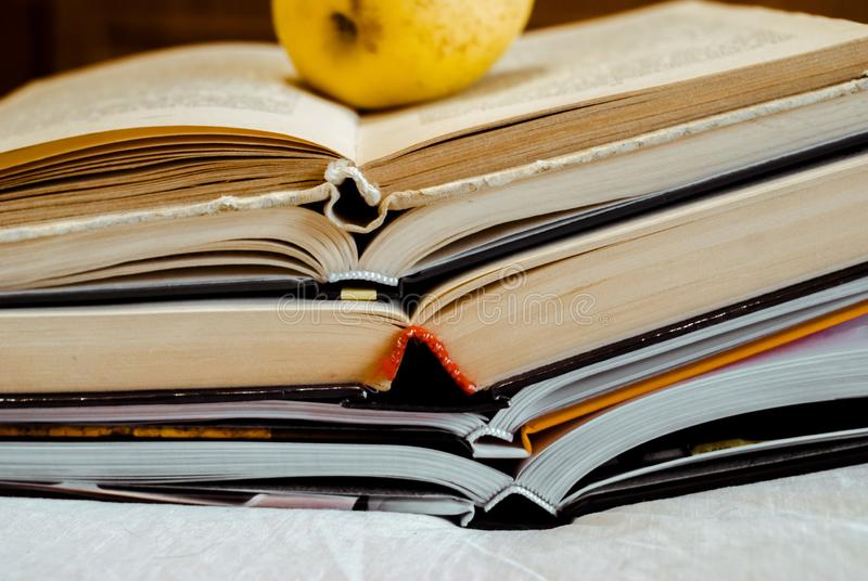 Lifestyle A stack of books on a white background. A yellow apple lies on a book. Copy space stock image
