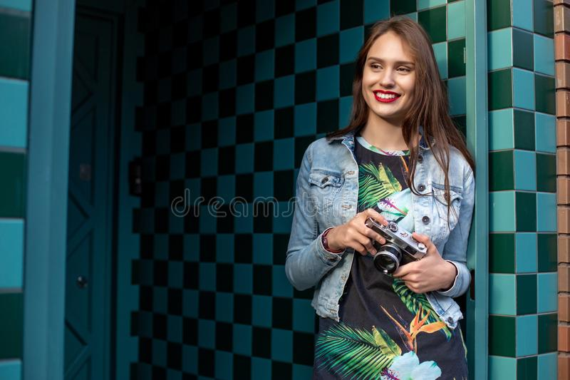 Lifestyle sunny fashion portrait of young stylish woman walking on street, with camera, smiling enjoy weekends. stock photography