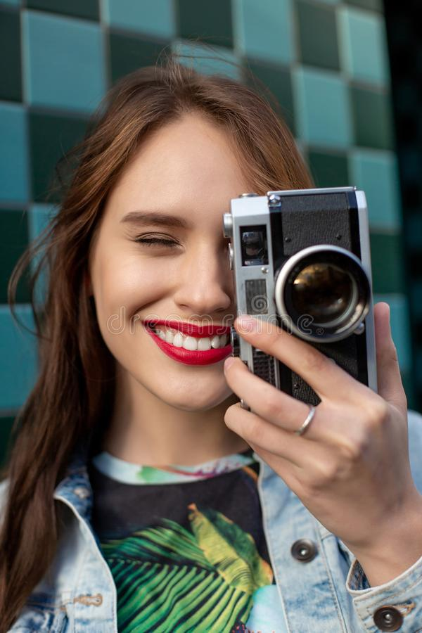 Lifestyle sunny fashion portrait of young stylish woman walking on street, with camera, smiling enjoy weekends. stock images