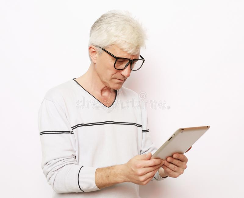 Lifestyle, tehnology and people concept: Happy senior man using digital tablet. stock images