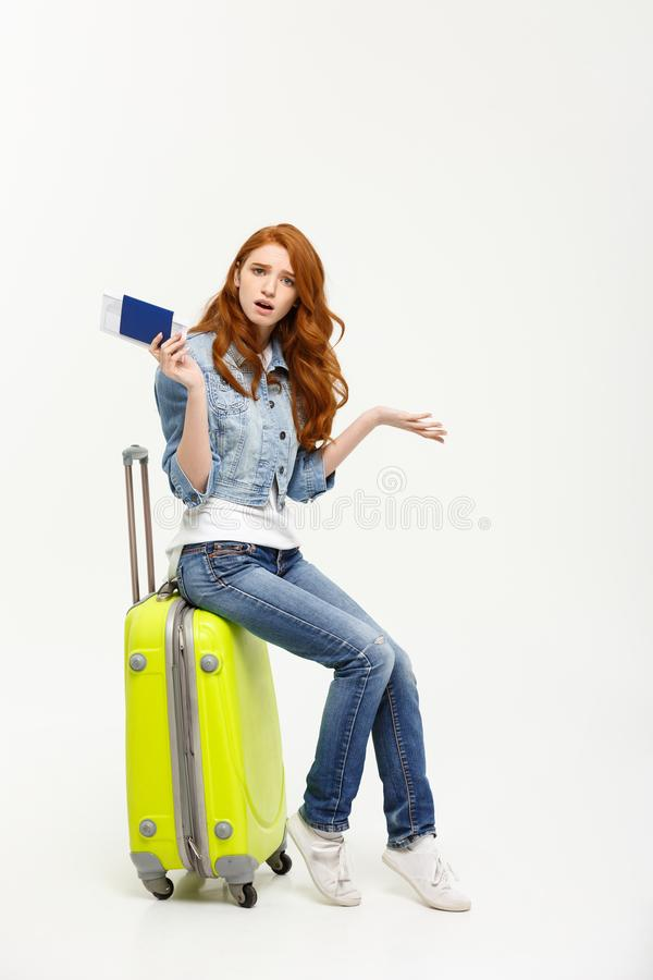 Lifestyle and travel Concept: Young beautiful caucasian woman is sitting on suitecase and waiting for her flight royalty free stock photography