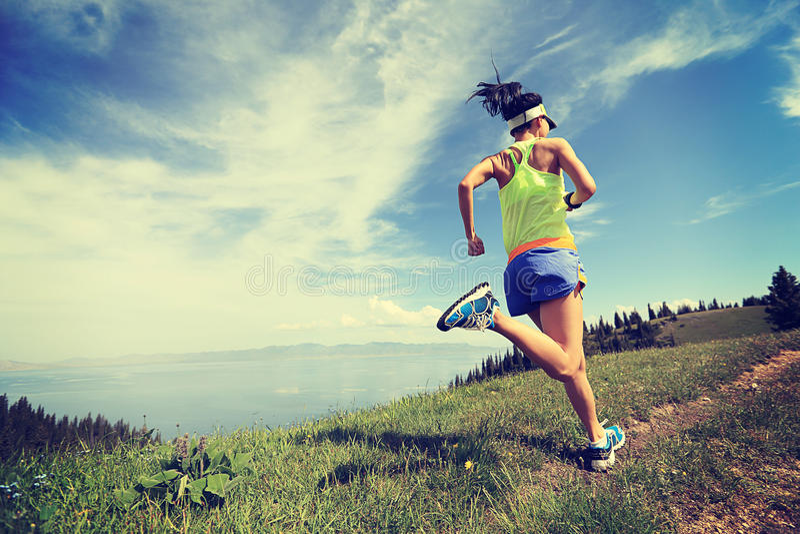 Lifestyle woman trail runner running on mountain peak stock photos