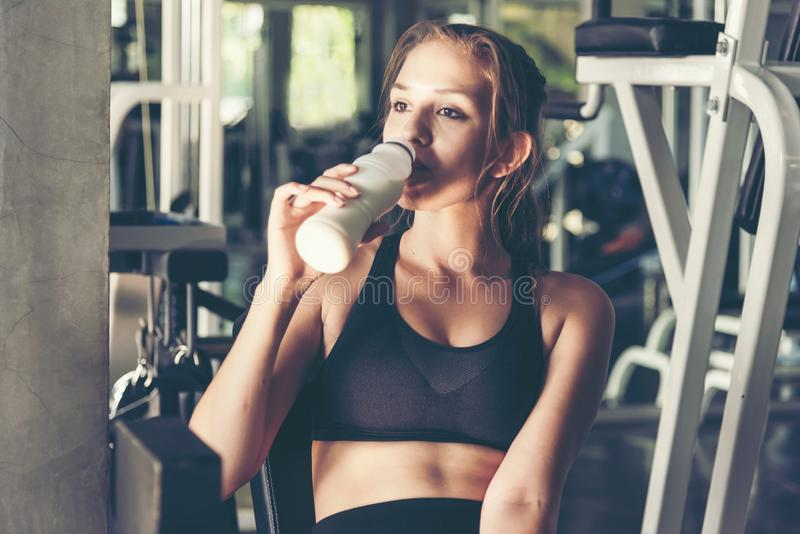 Lifestyle women drinking protein milk after exercise  at the gym workout for healthy care and body slim.  Fitness instructor exerc stock photos