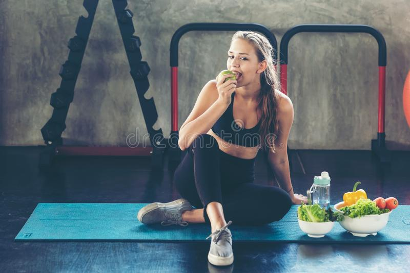 Lifestyle women eating green apple and fresh salad after exercise at the gym workout for healthy care and body slim. stock photo