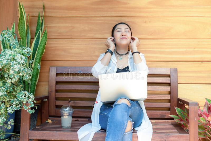 Lifestyle women freelance enjoy listening music and play laptop outdoors work space in the coffee shop for working . Lifestyle woman freelance enjoy listening stock photos