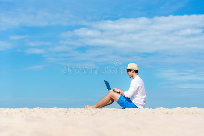 Lifestyle young asian man working on laptop while sitting chill on the beautiful beach, freelance working social on holiday summer. Summer and Vacation stock photos