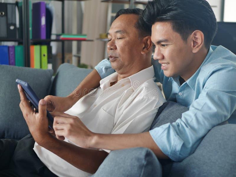 Lifestyles Famille Père et Fils passer des vacances ensemble jouent le téléphone portable dans la maison Bangkok Thaïlande photos stock