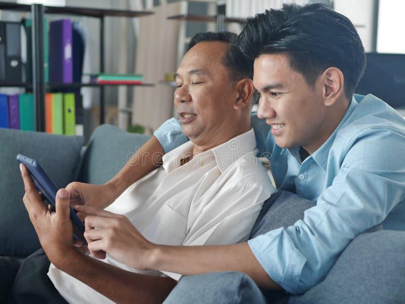 Lifestyles Famille Père et Fils passer des vacances ensemble jouent le téléphone portable dans la maison Bangkok Thaïlande photo stock