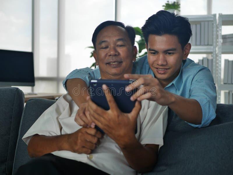 Lifestyles Famille Père et Fils passer des vacances ensemble jouent le téléphone portable dans la maison Bangkok Thaïlande photo libre de droits