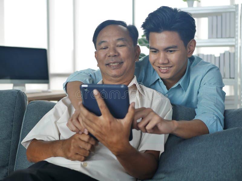 Lifestyles Famille Père et Fils passer des vacances ensemble jouent le téléphone portable dans la maison Bangkok Thaïlande photos libres de droits
