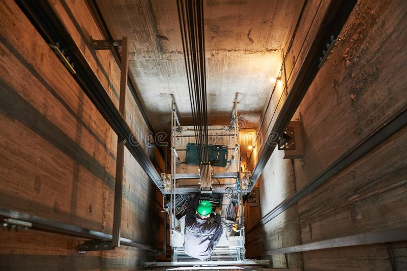 Lift machinist repairing elevator in lift shaft stock photography