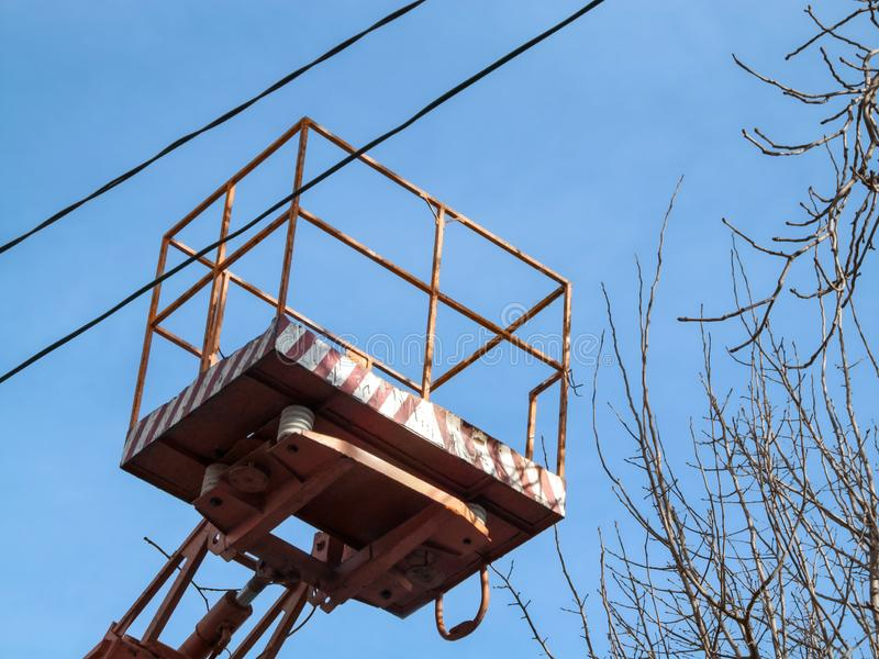 Lift-platform of the aerial device between electrical wires and bare branches of a tree against a blue sky. The concept of work in. The air using the mobile stock image
