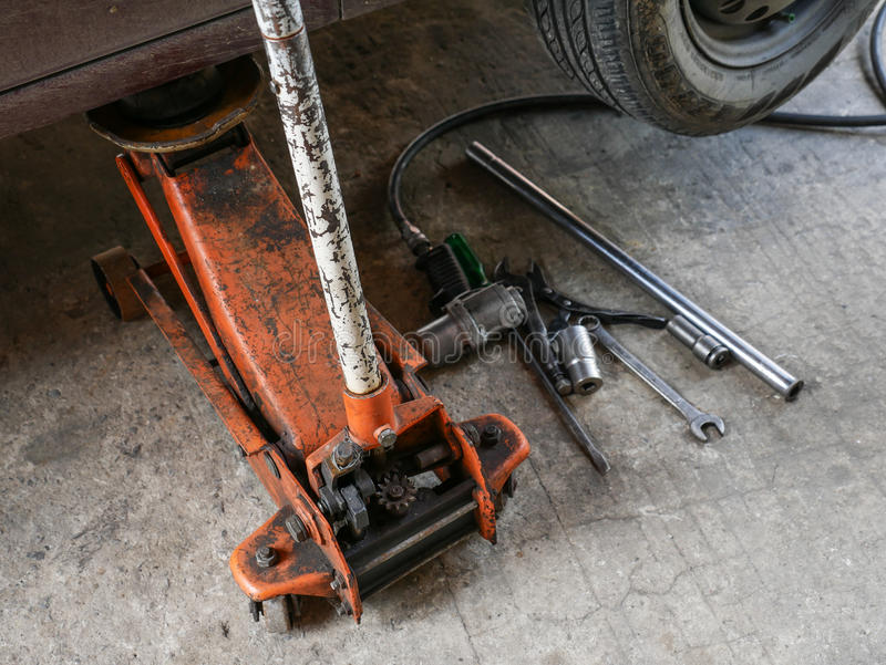 Lifted car by car jack tool for maintenance and repair. royalty free stock image