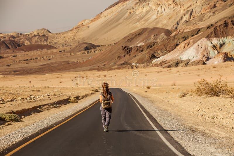 Liftervrouw die op een weg in de V.S. lopen stock foto's